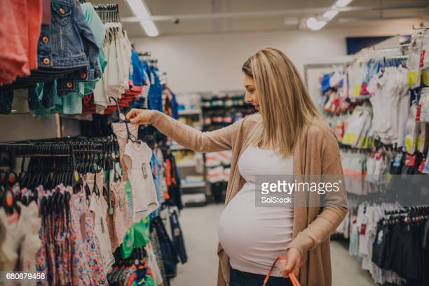 pregnant woman shopping - baby clothing stock pictures, royalty-free photos & images