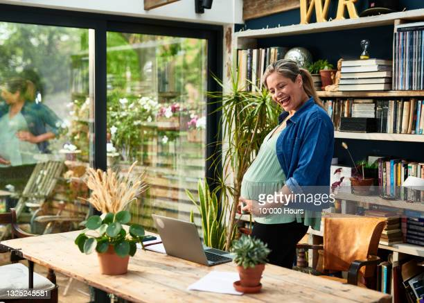 pregnant woman showing her bump in front of laptop - one mature woman only stock pictures, royalty-free photos & images