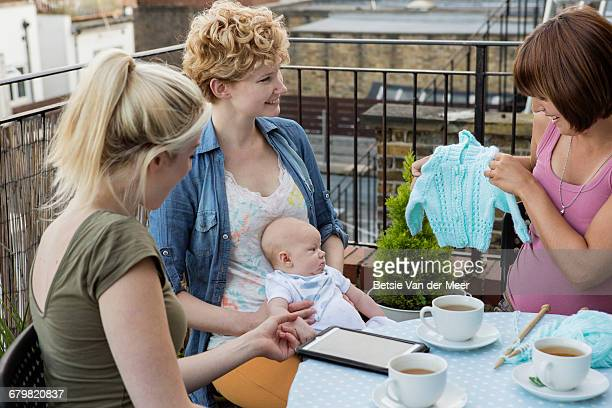 Pregnant woman shows her knitting to friends baby.