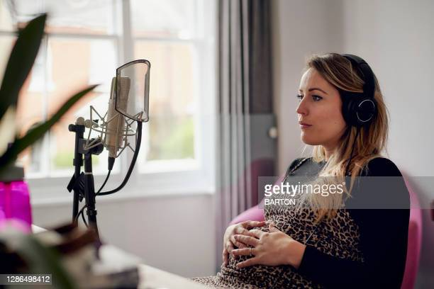 pregnant woman singing in home recording studio - one mid adult woman only stock pictures, royalty-free photos & images