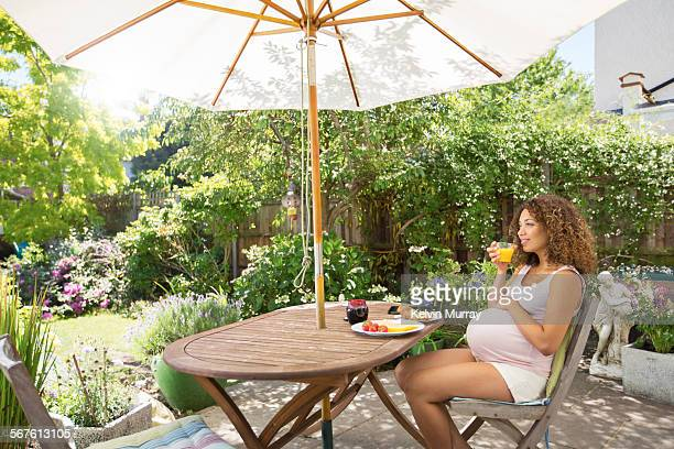 A pregnant woman sits outside to have breakfast