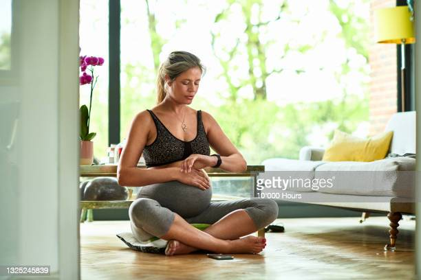 pregnant woman sitting cross-legged on floor checking fitness watch - one mature woman only stock pictures, royalty-free photos & images