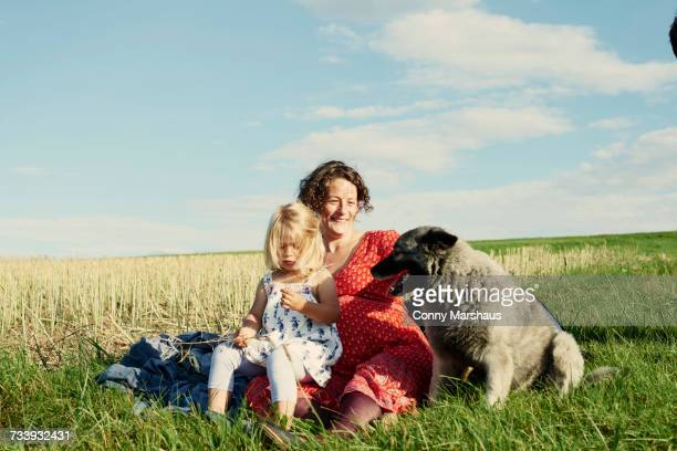 Pregnant woman sitting in field with toddler daughter and dog