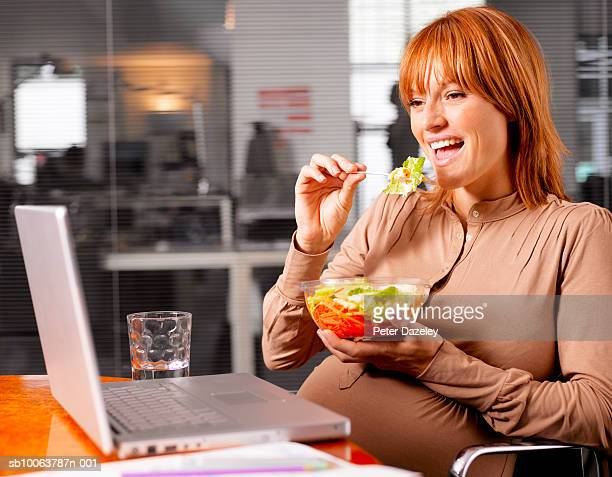 Pregnant woman sitting in front of laptop and eating salad