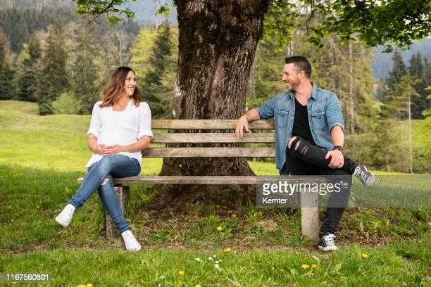 schwangere frau sitzt auf einer bank mit ihrem freund - sitzbank stock-fotos und bilder