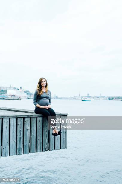 A pregnant woman sitting on a jetty