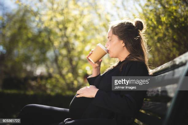pregnant woman sitting on bench - pregnant coffee stock pictures, royalty-free photos & images