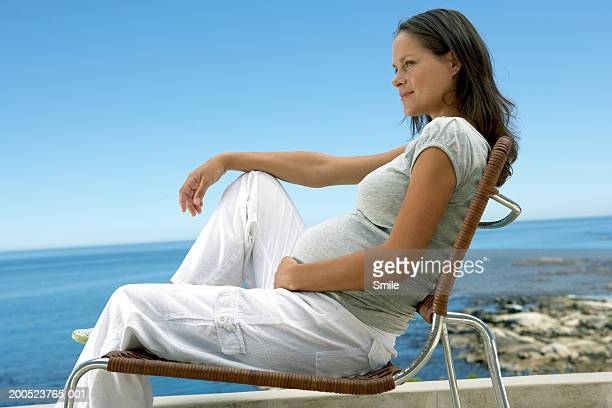 Pregnant woman sitting on chair, sea in background, side view.