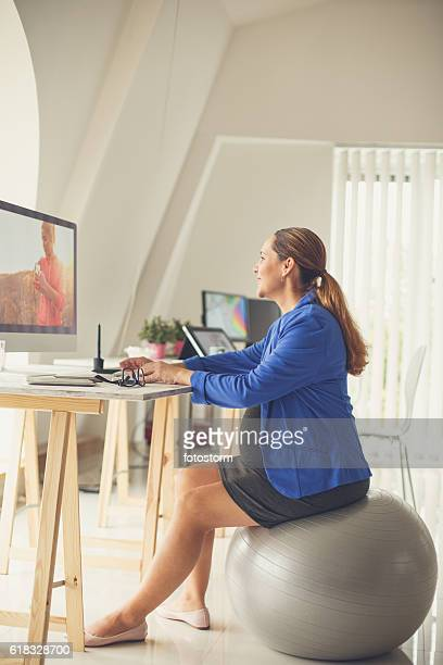 pregnant woman sitting on fitness ball at office - fitness ball stock pictures, royalty-free photos & images
