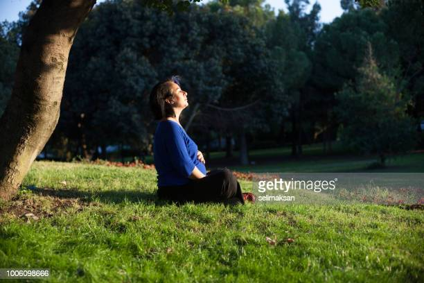 Pregnant Woman Sitting On Green Grasses In Public Park