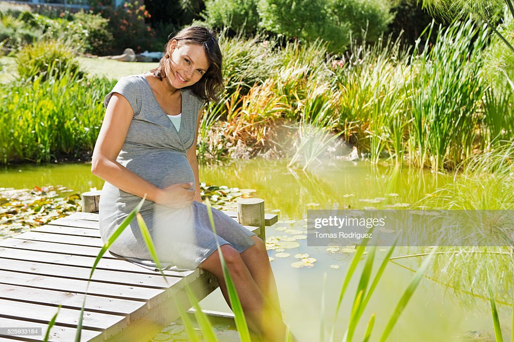 Pregnant woman sitting on jetty : Stock Photo