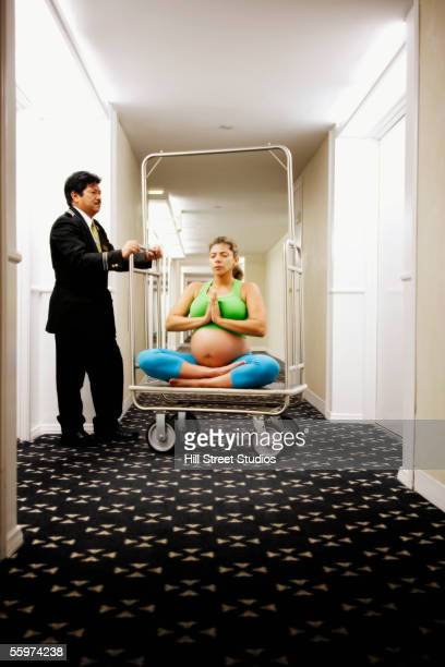 Pregnant woman sitting on luggage cart