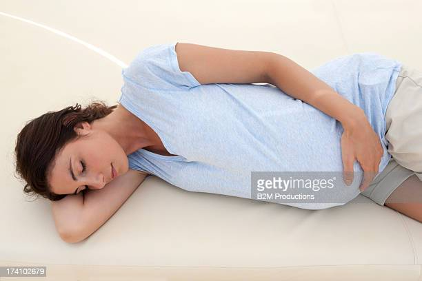 pregnant woman sleeping on bed - lying on side stock pictures, royalty-free photos & images