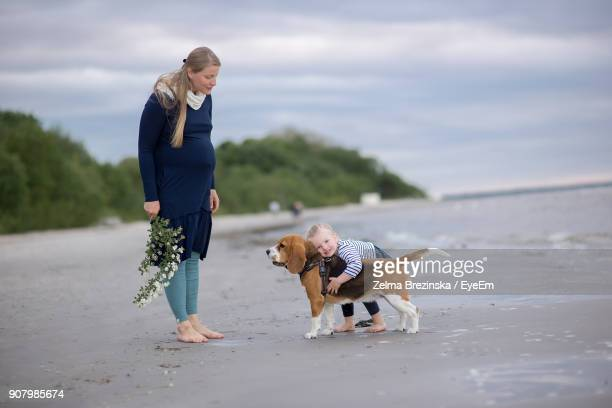 Pregnant Woman Standing By Daughter Playing With Dog At Beach Against Sky