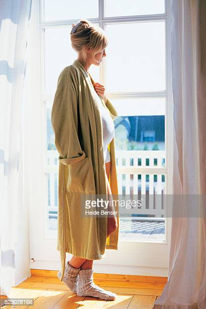 Pregnant woman standing by the window