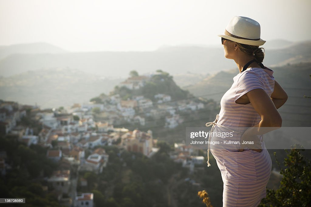 Pregnant woman standing with hand on hip, mountains in background : Stock Photo