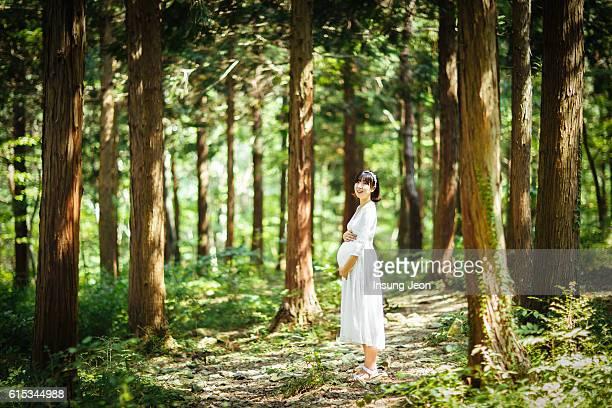 pregnant woman standingin the forest holding her belly - koreanischer abstammung stock-fotos und bilder