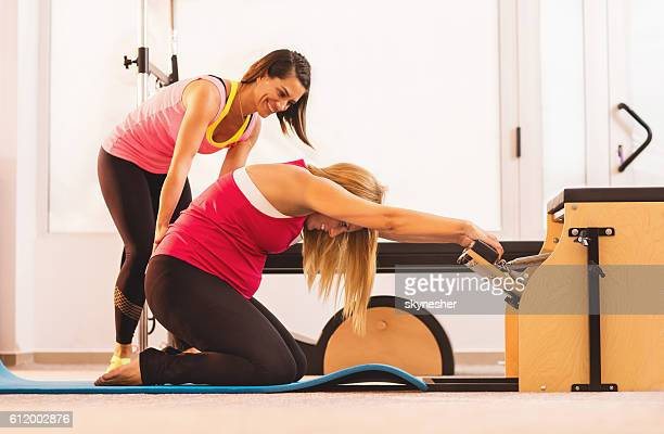 Pregnant woman stretching on Pilates chair with help of instructor.