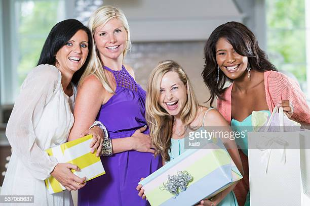 Pregnant woman surrounded by friends holding gifts