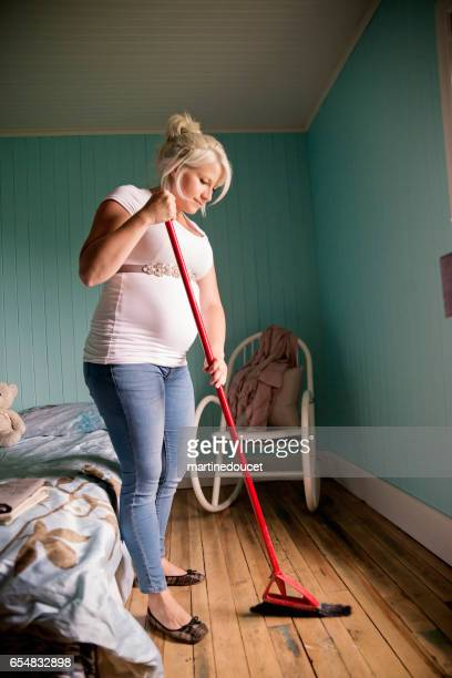 Pregnant woman sweeping the floor in home bedroom.