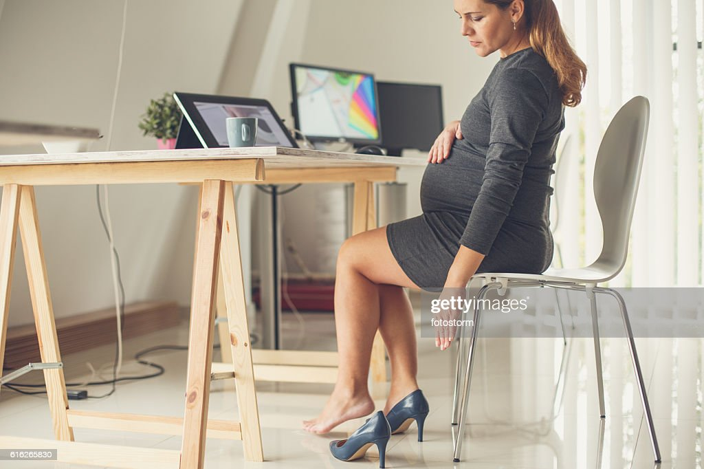 Pregnant woman taking off her shoes : Stock Photo