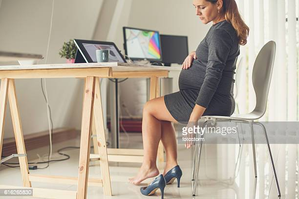Pregnant woman taking off her shoes