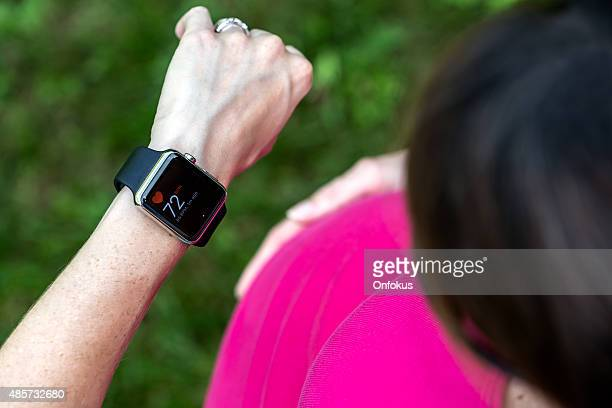 pregnant woman taking pulse on apple watch - apple watch stock pictures, royalty-free photos & images