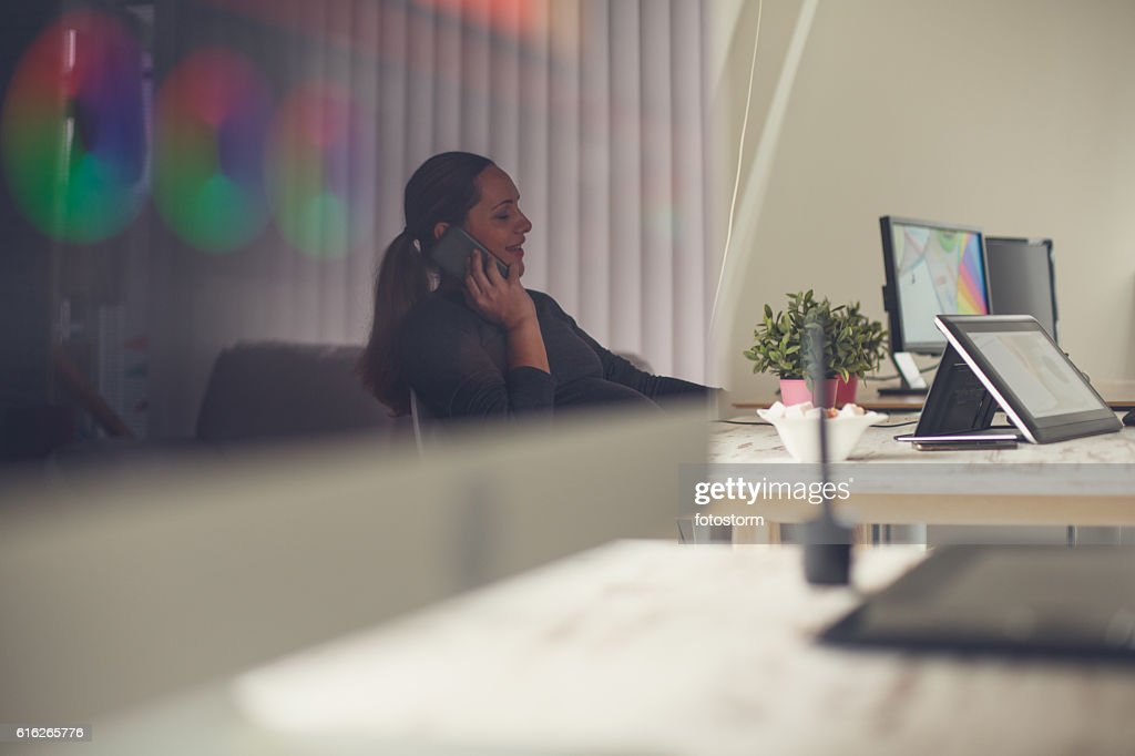 Pregnant woman talking on cellphone in office : Stock Photo