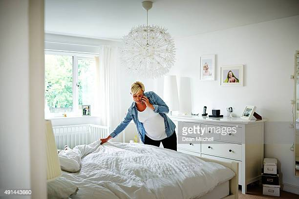 Pregnant woman talking on mobile phone and making bed