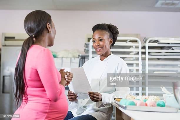 Pregnant woman talking to baker in commercial kitchen
