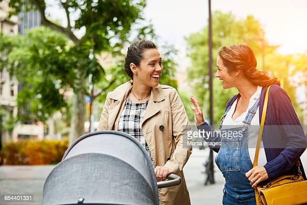 Pregnant woman talking to friend on sidewalk