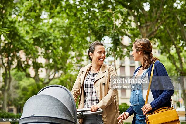 Pregnant woman talking to friends with stroller