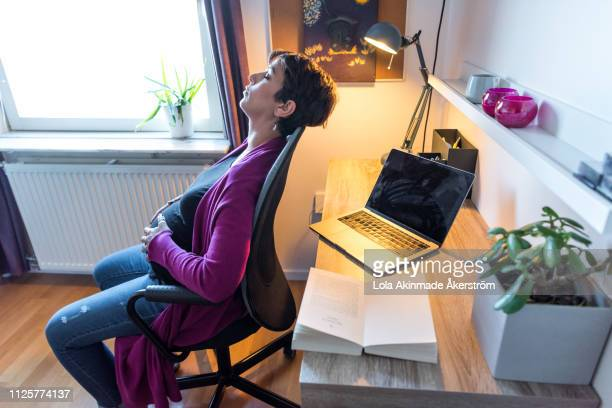 pregnant woman tired and resting on office chair - lola reve photos et images de collection