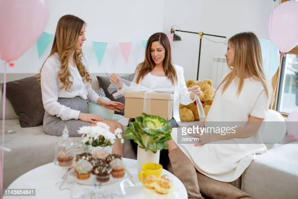 妊娠中の女性はベビーシャワーでギフトボックスに解くリボン - 外れる ストックフォトと画像