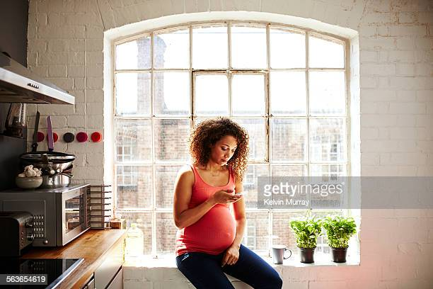 a pregnant woman uses her smartphone by a window - one young woman only stock pictures, royalty-free photos & images