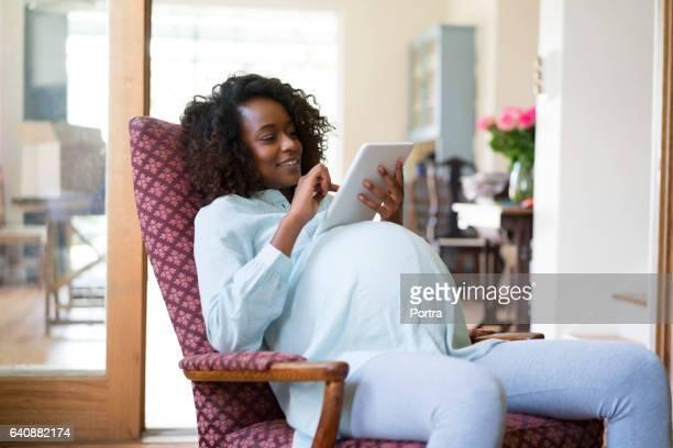 pregnant woman using digital tablet at home - femme noire enceinte photos et images de collection