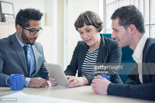 Pregnant woman using digital tablet with coworkers