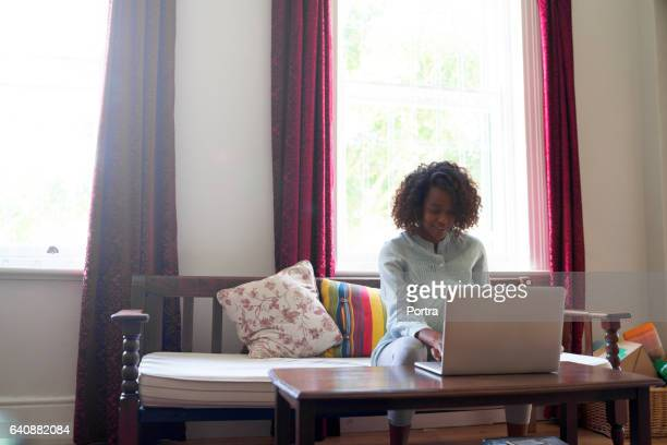 Pregnant woman using laptop at brightly lit home