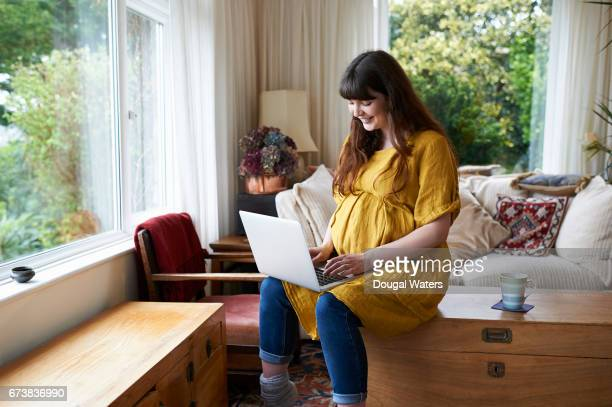 Pregnant woman using laptop at home.
