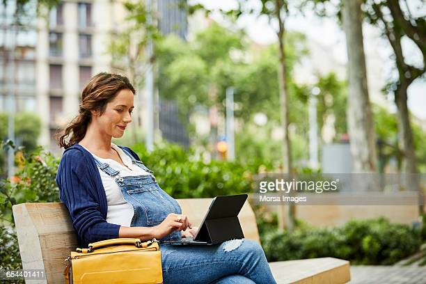 Pregnant woman using laptop while sitting on bench