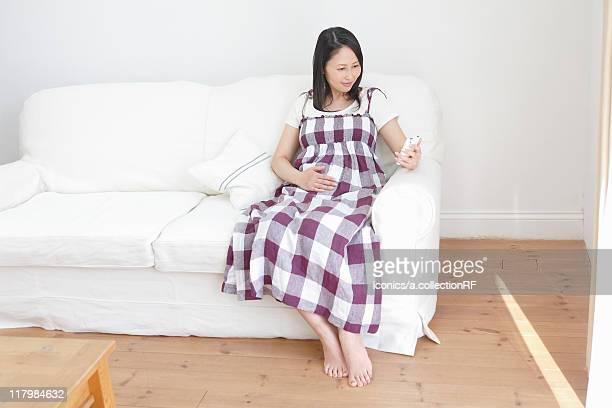Pregnant Woman Using Smart Phone on Sofa