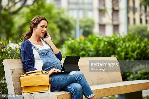 Pregnant woman using technologies on bench