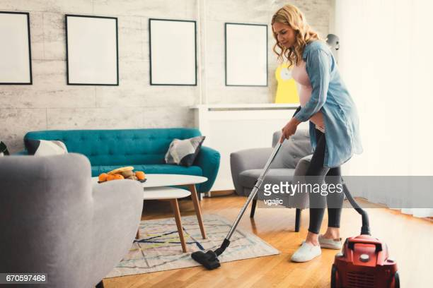 pregnant woman vacuuming carpet - suction tube stock pictures, royalty-free photos & images