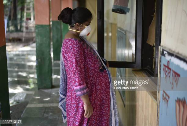 Pregnant woman waits in front of the registration window for a Covid-19 test, at a centre in the MCD primary school at Turkman Gate on June 24, 2020...