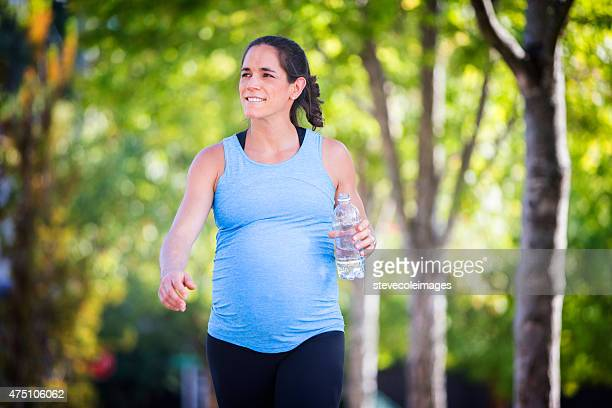 Pregnant woman walking and carrying a bottle of water.