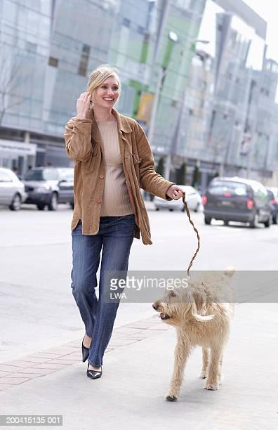 Pregnant woman walking dog, smiling