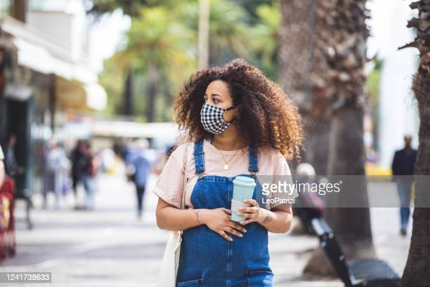 pregnant woman walking in the city in a sunny day protecting herself with a cloth face mask - reusable stock pictures, royalty-free photos & images