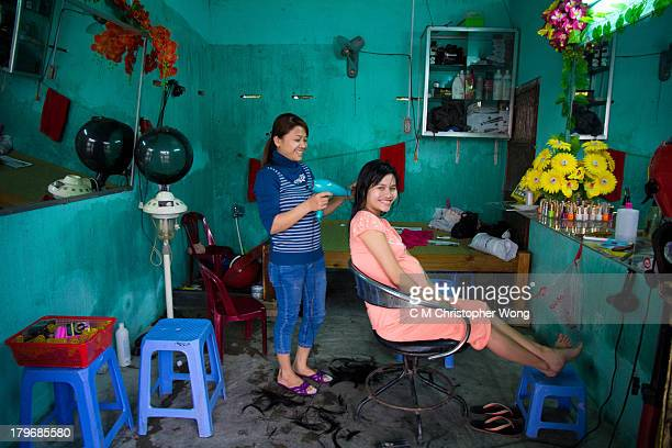 Pregnant woman was getting a hair cut and blow dry in a road side one-seat salon, plastic flowers, molded wall, plastic stools, thong
