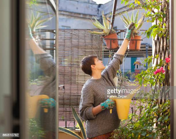 Pregnant woman watering plants on the terrace