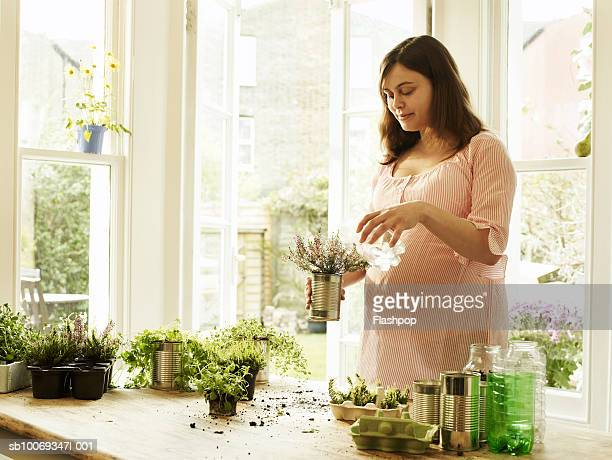 Pregnant woman watering potted plant